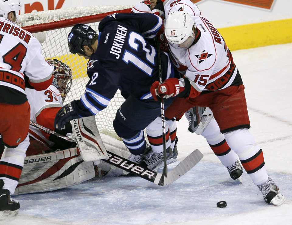 Photo - Carolina Hurricanes' Tuomo Ruutu (15) knocks Winnipeg Jets' Olli Jokinen (12) off the rebound in front of goaltender Justin Peters (35) during the first period of their NHL hockey game in Winnipeg, Manitoba, Thursday, April 18, 2013. (AP Photo/The Canadian Press, John Woods)