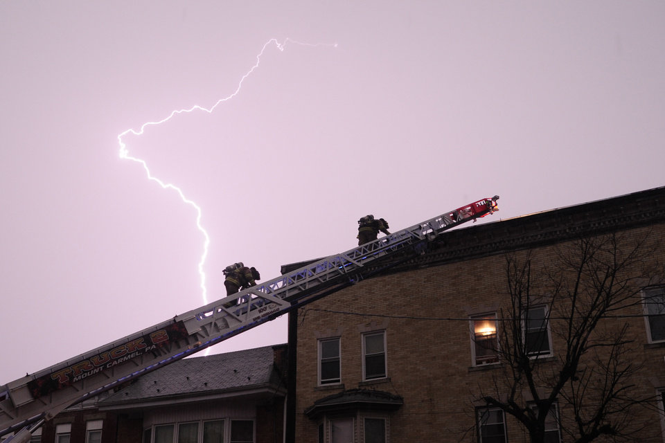 Photo -   Firefighters Jim Williams, left, and Mike Ledger descend down the ladder of Mount Carmel Truck 2 at the scene of a possible building fire in Mount Carmel, Pa., after the building was struck by lightning during a storm on Thursday, July 26, 2012. Mount Carmel Fire Chief Jack Williams Sr., who had command, said firefighters left the roof in under three minutes once it was confirmed the roof was not on fire. He added there was no damage to the building. (AP Photo/The News-Item, Larry Deklinski)