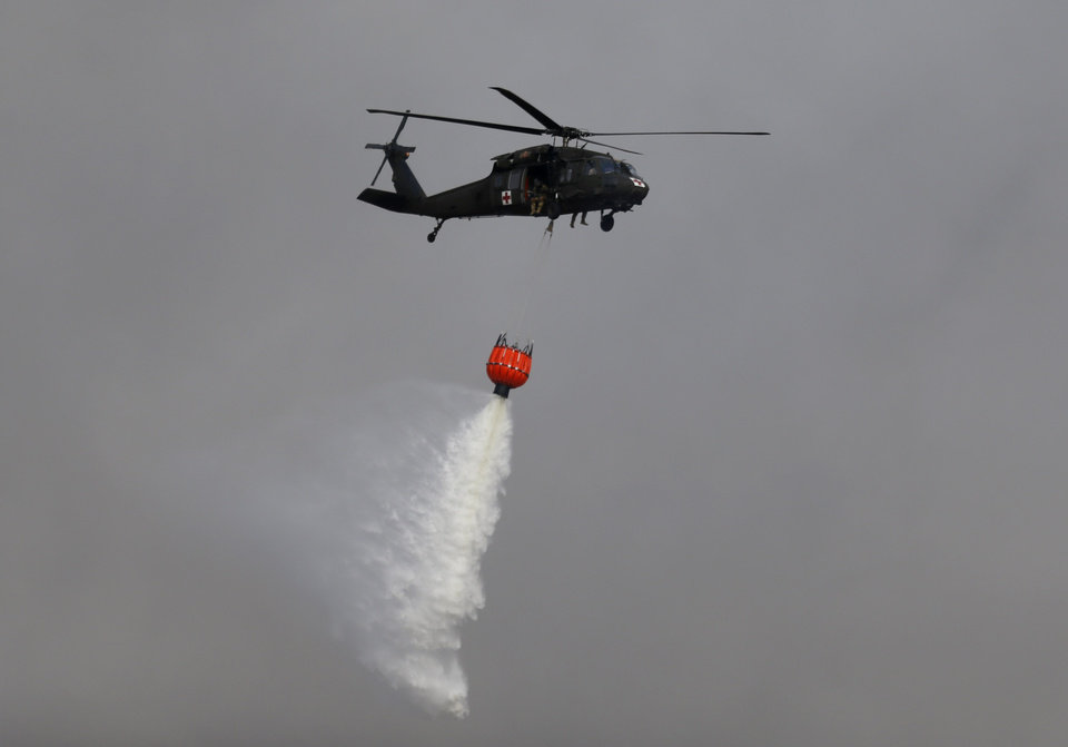 Photo -  A helicopter drops water on the fire. [Photo by Sarah Phipps, The Oklahoman]