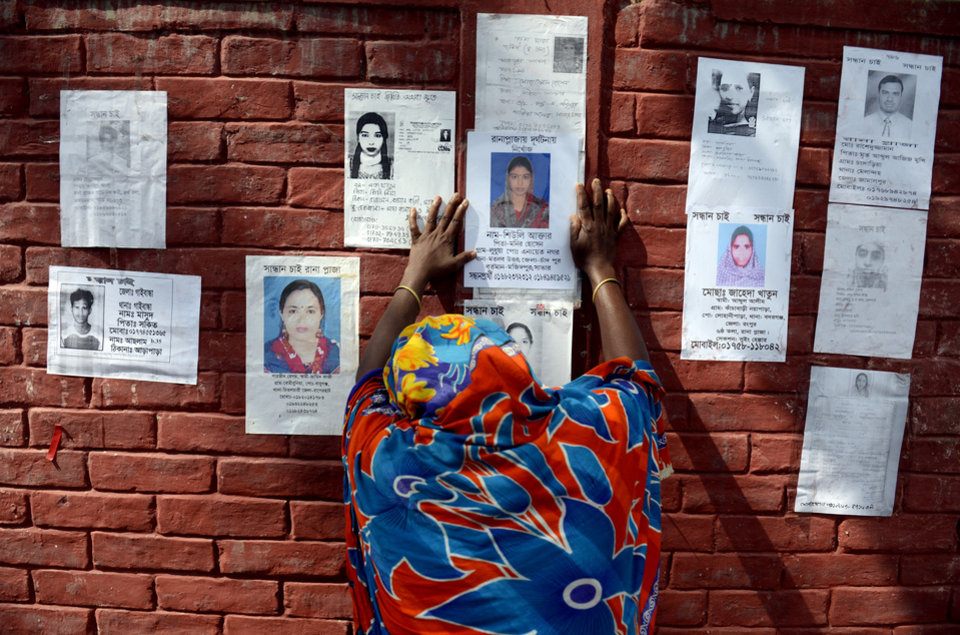 Photo - A woman grieves as she sticks a pposter of a portrait of her family member on the wall of a school turned make-shift morgue on Tuesday 30, April, 2013 in Savar, near Dhaka, Bangladesh. Emergency workers hauling large concrete slabs from a collapsed 8-story building said Tuesday they expect to find many dead bodies when they reach the ground floor, indicating the death toll will be far more than the official 386. One estimate said it could be as high as 1,400. The illegally constructed, 8-story Rana Plaza collapsed on the morning of April 24, bringing down the five garment factories inside.(AP Photo/Ismail Ferdous)