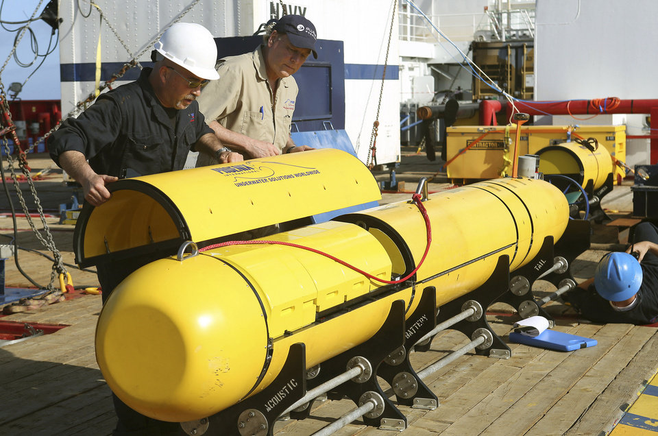 Photo - In this Monday, April 14, 2014, photo provided by the Australian Defense Force Phoenix International's Chris Minor, left, and Curt Newport inspect an autonomous underwater vehicle before it is deployed from ADV Ocean Shield in the search of the missing Malaysia Airlines Flight 370 in the southern Indian Ocean. The search area for the missing Malaysian jet has proved too deep for the robotic submarine which was hauled back to the surface of the Indian Ocean less than half way through its first seabed hunt for wreckage and the all-important black boxes, authorities said on Tuesday. (AP Photo/Australian Defense Force, Lt. Kelli Lunt) EDITORIAL USE ONLY