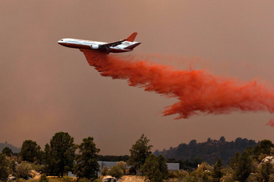 Photo - Tanker 910 makes a retardant drop Yarnell Hill Fire to help protect the Double Bar A Ranch near Peeples Valley, Ariz., Sunday, June 30, 2013. The fire started Friday and picked up momentum as the area experienced high temperatures, low humidity and windy conditions. It has forced the evacuation of residents in the Peeples Valley area and in the town of Yarnell. (AP Photo/The Arizona Republic, Tom Story)