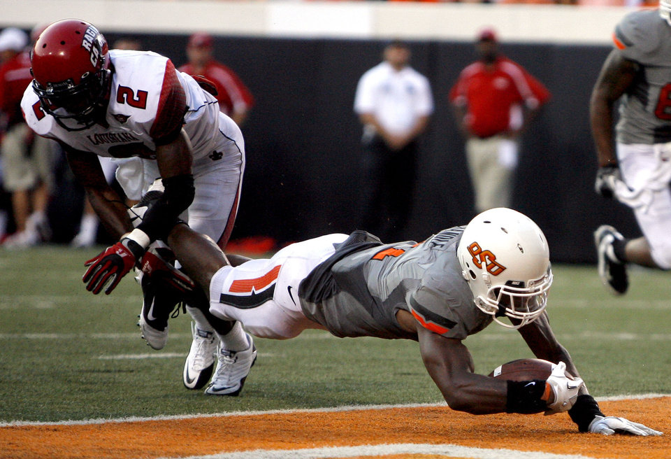 Photo - Oklahoma State's Joseph Randle scores a touchdown in front of La.-Lafayette's Jemarlous Moten during their game Saturday in Stillwater. Photo by Sarah Phipps, The Oklahoman