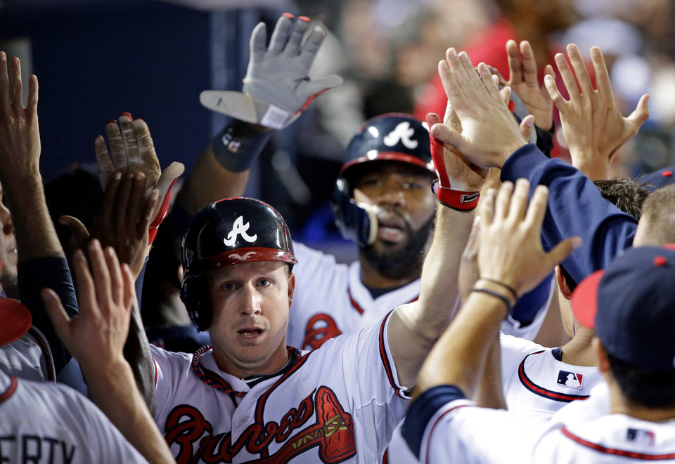 Photo - Atlanta Braves' Elliot Johnson, left, and Jason Heyward, rear right, high-five teammates after scoring off a double by Evan Gattis in the second inning of a baseball game against the Philadelphia Phillies, Thursday, Sept. 26, 2013, in Atlanta. (AP Photo/David Goldman)