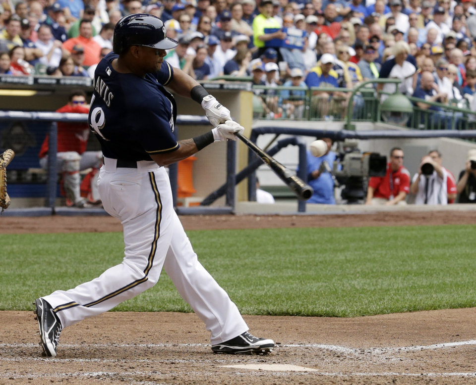 Photo - Milwaukee Brewers' Khris Davis hits a two-RBI single during the fifth inning of a baseball game against the Washington Nationals Wednesday, June 25, 2014, in Milwaukee. (AP Photo/Morry Gash)