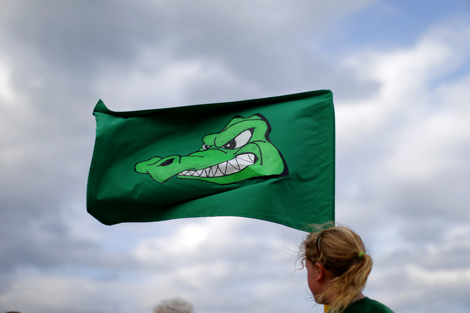 Photo -  Reagan Baskin, 11, holds a flag for her Crocness Monster team before the team takes part in its sixth Cardboard Boat Regatta as part of the LibertyFest events at Arcadia Lake. PHOTO BY BRYAN TERRY, THE OKLAHOMAN   Bryan Terry -  THE OKLAHOMAN