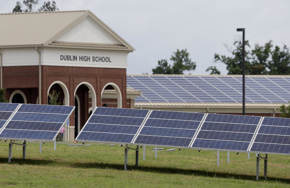 Photo - Newly installed solar panels in front of Dublin High School are shownTuesday, June 18, 2013, in Dublin, Ga. The solar panels being installed at the rural Georgia school are challenging one of its biggest electric monopolies. For years, Southern Co. subsidiary Georgia Power has claimed that no firm except itself can sell power in its state-designated territory.   (AP Photo/John Bazemore)