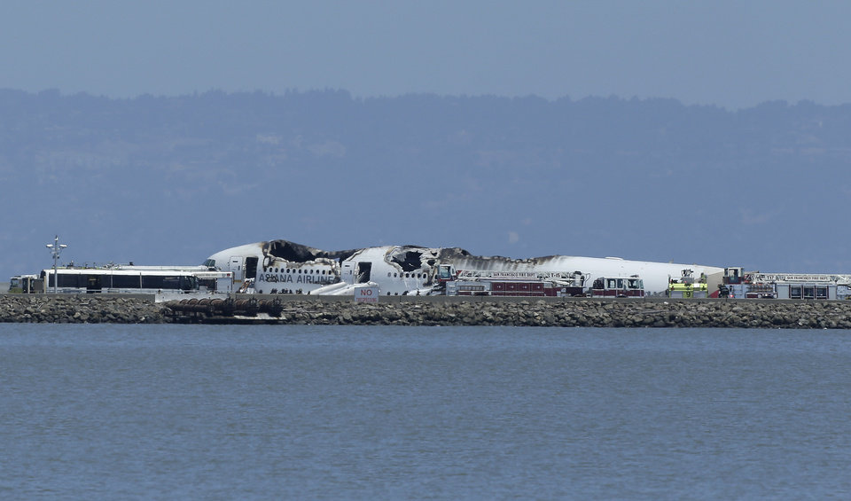 Photo - The wreckage of Asiana Flight 214 is seen after it crashed at San Francisco International Airport in San Francisco, Saturday, July 6, 2013. (AP Photo/Jeff Chiu)