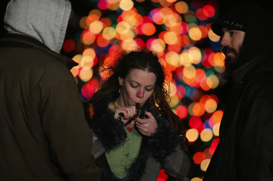 Photo - Nicola Thompson, center, lights her pipe with Toby Tackett, right, and Scott Newsome as they celebrate legalization of marijuana in Seattle, Washington, Thursday, Dec. 6, 2012, at the Seattle Center International Fountain. Thompson and Tackett are part of Think Piece Productions and are documenting the legalization process in Washington state. (AP Photo/Colin Diltz, The Seattle Times)