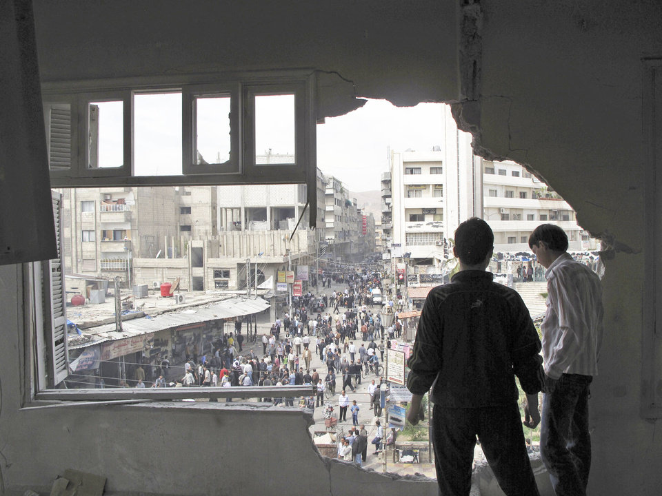 Syrian youth stand in a building damaged by tank shells in Damascus, Syria, after a raid by Syrian troops in April 2012. AP File Photo