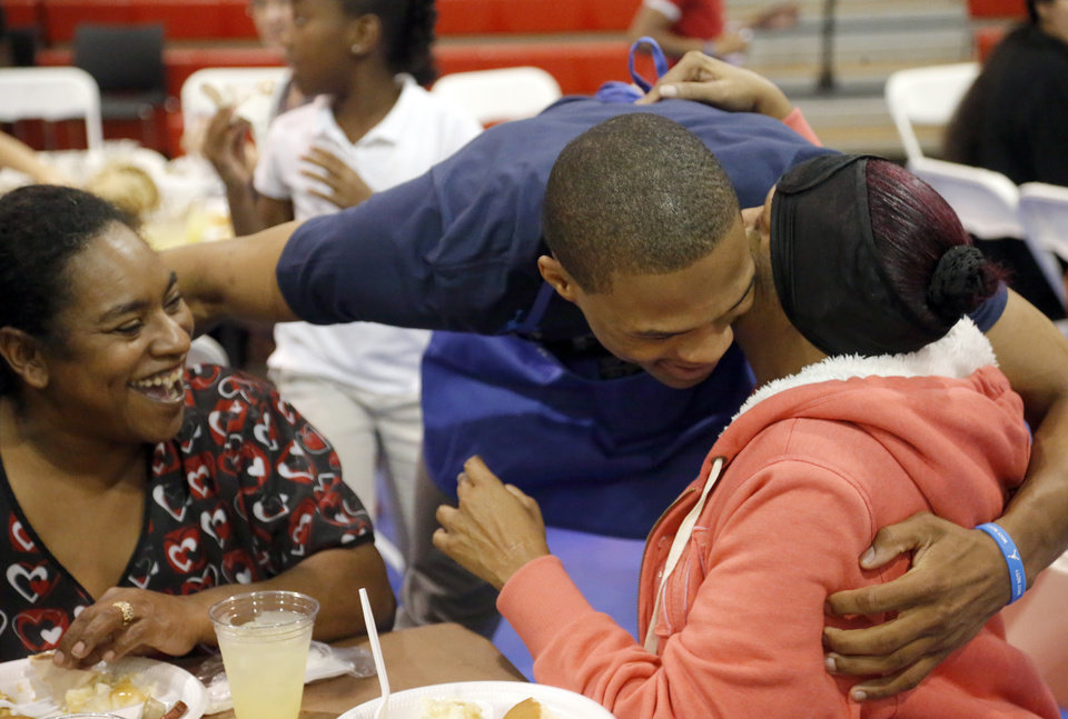 Photo - OKLAHOMA CITY THUNDER NBA BASKETBALL PLAYER / CHARITY: Oklahoma City's Russell Westbrook hugs Mary Thompson as Tywauna Douglas looks on during a Thanksgiving dinner at the Boys & Girls Club of Oklahoma County in Oklahoma CIty,  Tuesday, Nov. 20, 2012. Photo by Sarah Phipps, The Oklahoman