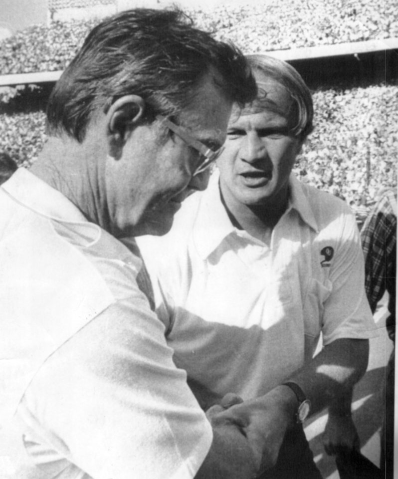 "Caption reads ""A grim Texas coach Darrell Royal congratulates Sooner chief Barry Switzer after the game."" Photographer unknown. Date photo was taken unknown. Photo published in The Daily Oklahoman 10-12-1975 and 10-9-1976 and the Oklahoma City Times 10-9-1976."