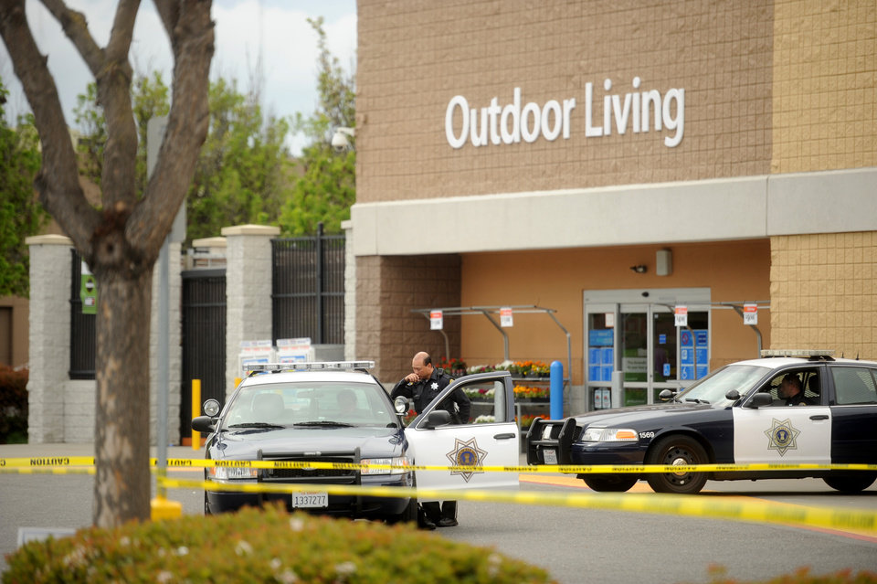 Photo - Police cars maintain a perimeter around a San Jose, Calif., Walmart after a motorist drove through a store entrance and began assaulting shoppers on Sunday, March 31, 2013. Four people sustained injuries during the attack according to a police spokesman. (AP Photo/Noah Berger)