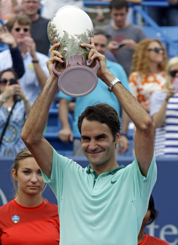 Photo - Roger Federer, from Switzerland, holds the championship trophy after defeating David Ferrer, from Spain, 6-3, 1-6, 6-2, in the final match at the Western & Southern Open tennis tournament, Sunday, Aug. 17, 2014, in Mason, Ohio. (AP Photo/Al Behrman)