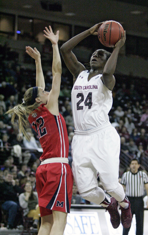 Photo - South Carolina's Aleighsa Welch (24) drives for the basket  as Ole Miss's Gracie Frizzell (12)  tries to block during the first half of an NCAA college basketball game Thursday, Jan. 30, 2014, in Columbia, S.C. (AP Photo/Mary Ann Chastain)