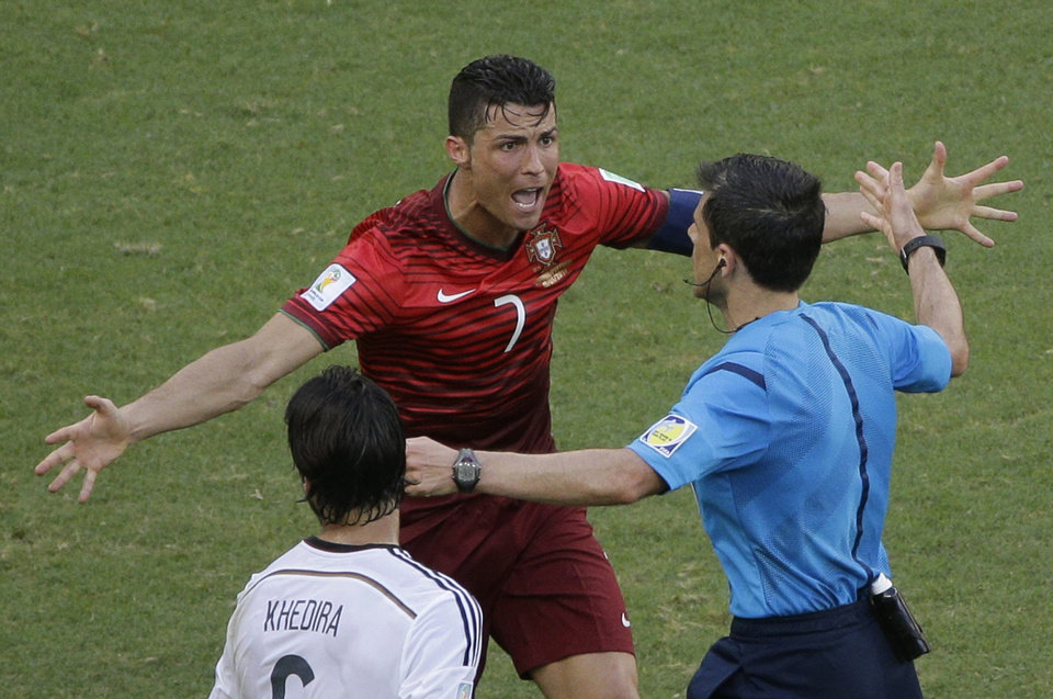 Photo - Portugal's Cristiano Ronaldo protests to referee Milorad Mazic from Serbia during the group G World Cup soccer match between Germany and Portugal at the Arena Fonte Nova in Salvador, Brazil, Monday, June 16, 2014. (AP Photo/Christophe Ena)