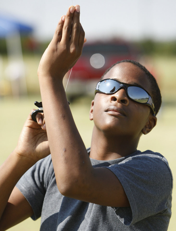 Photo - Right: Chad Jones, 13, maneuvers his kite during KiteFest on Saturday.