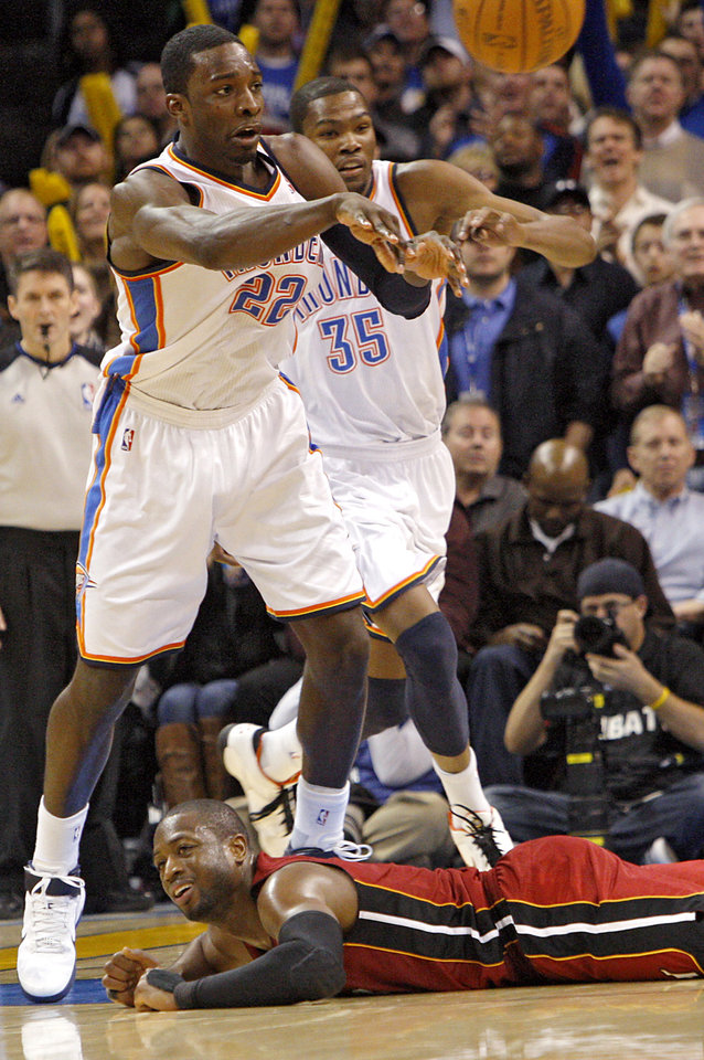 Photo - Oklahoma City's Jeff Green picks up a loose ball in front of Miami's Dwyane Wade during their NBA basketball game at the OKC Arena in Oklahoma City on Thursday, Jan. 30, 2011. The Heat beat the Thunder 108-103. Photo by John Clanton, The Oklahoman