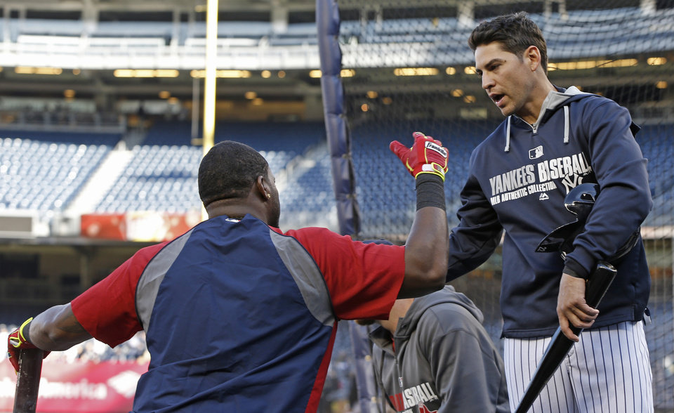 Photo - Boston Red Sox designated hitter David Ortiz, left, talks with former teammate New York Yankees' Jacoby Ellsbury behind the batting cage before a baseball game at Yankee Stadium in New York, Thursday, April 10, 2014.  (AP Photo/Kathy Willens)