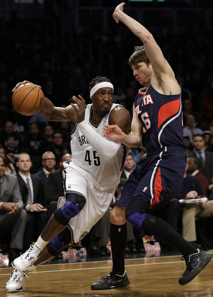 Brooklyn Nets forward Gerald Wallace (45) drives toward the basket as Atlanta Hawks guard Kyle Korver (26) defends in the first half of their NBA basketball game at the Barclays Center, Friday, Jan. 18, 2013, in New York. (AP Photo/Kathy Willens)