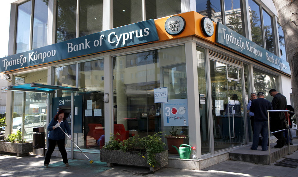 Photo - A woman sweeps as people, right, wait outside a branch of Bank of Cyprus in Nicosia, Cyprus, Thursday, March 28, 2013. Bank branches across the country were being replenished with cash, and are scheduled to open for six hours at noon (10:00 GMT). Systems were frozen pending the official noon opening, and guards from a private security firm were reinforcing police outside some ATMs and banks in Nicosia. (AP Photo/Petros Karadjias)