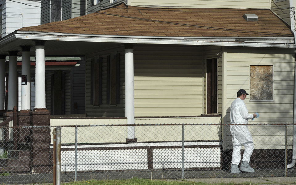 Photo - A member of the FBI evidence response team searches a house near the home where three women were held Wednesday, May 8, 2013, in Cleveland. A man was charged with four counts of kidnapping — covering all three captives and the daughter born to one of them while she was held — and three counts of rape against the three women.  (AP Photo/Roadell Hickman)