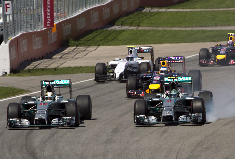 Photo - Mercedes driver Nico Rosberg from Germany, right, locks his brakes as he heads into the Senna corner with teammate Lewis Hamilton, left,  from Great Britain during the Canadian Grand Prix Sunday, June 8, 2014 in Montreal. (AP Photo/The Canadian Press, Ryan Remiorz)