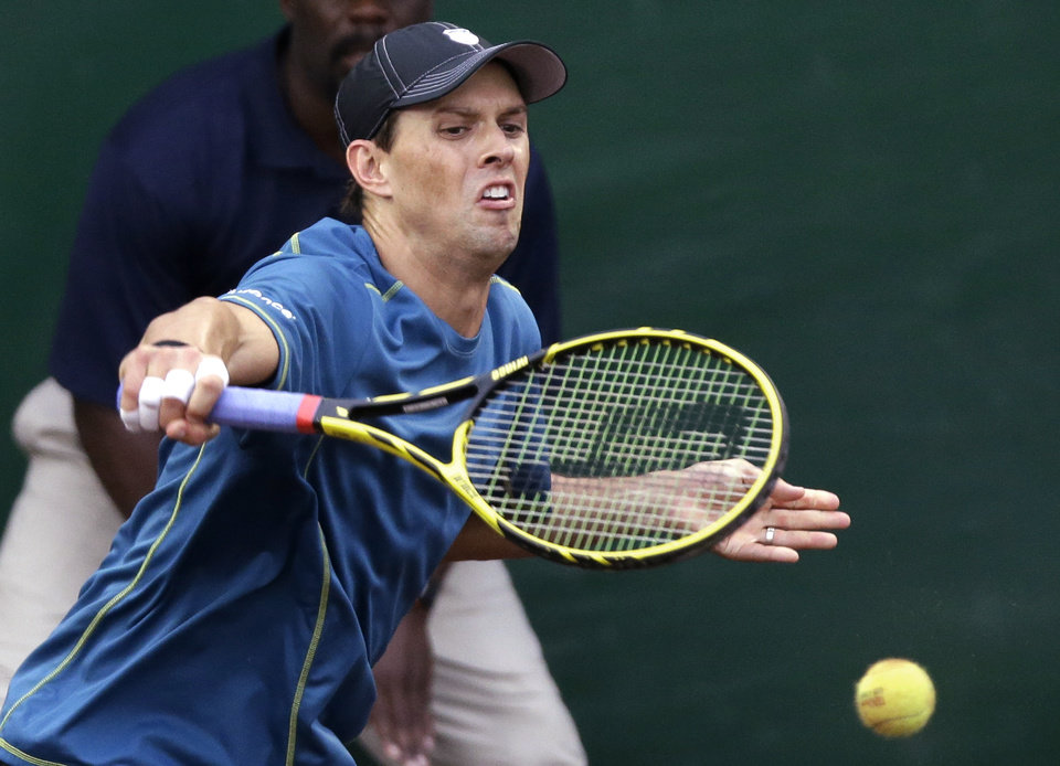Photo - Mike Bryan, of the United States, returns a shot in the doubles final between Mike and Bob Bryan and Spain's Fernando Vedasco and David Marrero at the U.S. Men's Clay Court Championship tennis tournament, Saturday, April 12, 2014, in Houston. (AP Photo/Pat Sullivan)