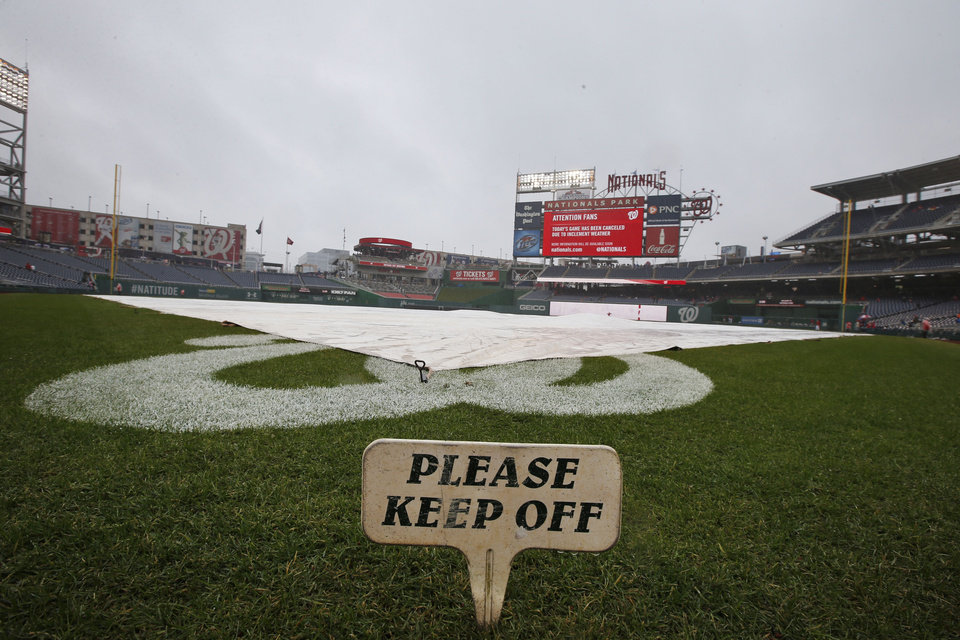 Photo - The field is covered before an exhibition baseball game between the Washington Nationals and the Detroit Tigers at Nationals Park Saturday, March 29, 2014, in Washington. The game was canceled due to weather. (AP Photo/Alex Brandon)