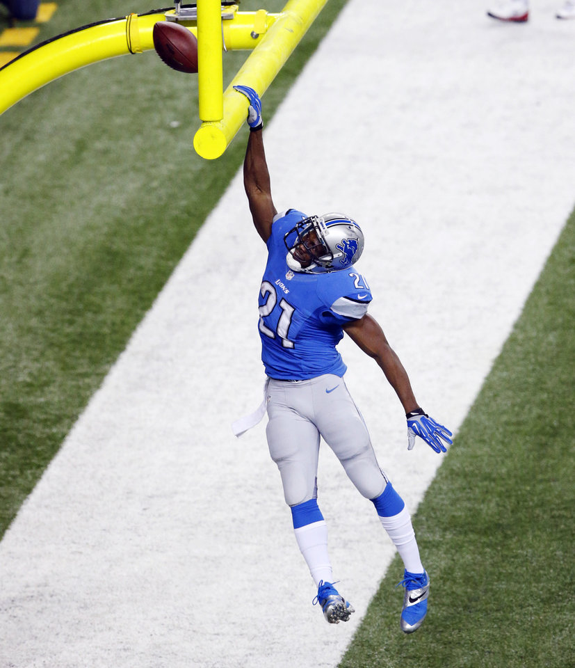 Photo - Detroit Lions running back Reggie Bush (21) dunks the football on the goal post after his 14-yard touchdown run during the first quarter of an NFL football game against the Baltimore Ravens in Detroit, Monday, Dec. 16, 2013. (AP Photo/Paul Sancya)