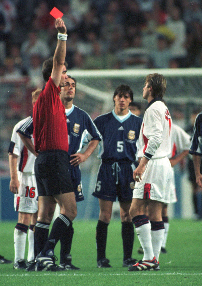 Photo - FILE - In this  June 30, 1998 file photo, England's David Beckham receives a red card from Danish referee Kim Milton Nielsen, during England's World Cup second round soccer match against Argentina, in Saint Etienne,  France. On this day: Beckham becomes public enemy number one in England, after he gets a red card for kicking Argentina's Diego Simeone. England lost on penalties after the match ended 2-2. (AP Photo/Denis Doyle, File)