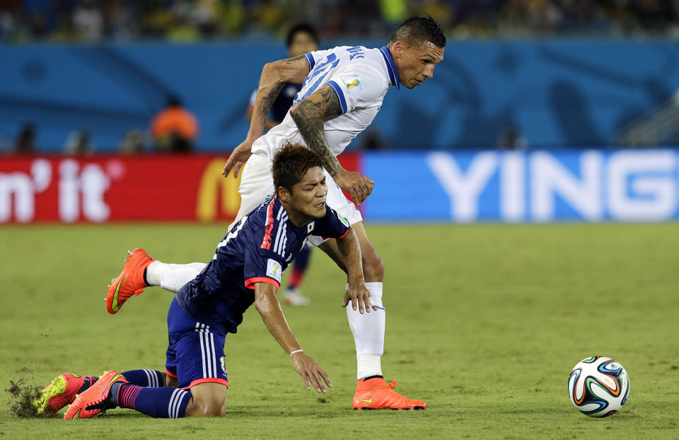 Photo - Greece's Jose Holebas, right, pulls down Japan's Yoshito Okubo while chasing the ball during the group C World Cup soccer match between Japan and Greece at the Arena das Dunas in Natal, Brazil, Thursday, June 19, 2014.  (AP Photo/Shuji Kajiyama)