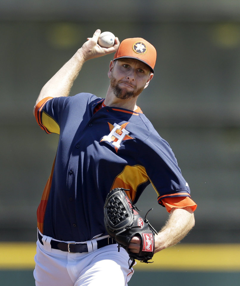 Photo - Houston Astros starting pitcher Scott Feldman warms up before a spring exhibition baseball game against the Washington Nationals in Kissimmee, Fla., Sunday, March 16, 2014. (AP Photo/Carlos Osorio)