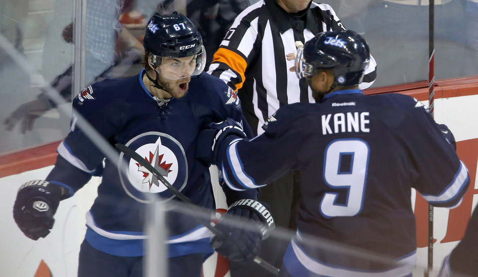 Photo - Winnipeg Jets' Michael Frolik (67) celebrates with Evander Kane (9) after scoring against the Dallas Stars' during first period NHL action at the MTS Centre in Winnipeg, Manitoba,  Sunday, March 16, 2014. (AP Photo/The Canadian Press, Trevor Hagan)