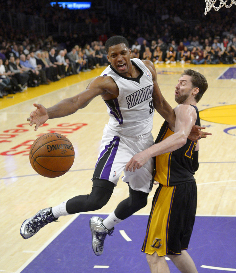 Photo - Sacramento Kings forward Rudy Gay, left, reaches for a loose ball along with Los Angeles Lakers center Pau Gasol, of Spain, during the first half of an NBA basketball game on Friday, Feb. 28, 2014, in Los Angeles. (AP Photo/Mark J. Terrill)