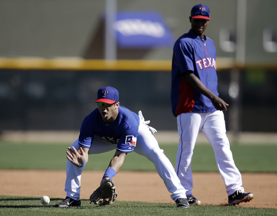 Photo - Seattle Seahawks quarterback Russell Wilson, left, fields a ground ball as Texas Rangers second baseman Jurickson Profar, right, stands near during spring training baseball practice, Monday, March 3, 2014, in Surprise, Ariz. (AP Photo/Tony Gutierrez)