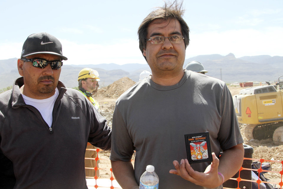 Photo - Alamogordo residents Armando Ortega, left, and Raul Ruiz pose for a photograph with a cartridge they found buried in a landfill in Alamogordo, N.M., Saturday, April 26, 2014. Producers of a documentary dug in an southeastern New Mexico landfill in search of millions of cartridges of the Atari 'E.T. the Extra-Terrestrial' game that has been called the worst game in the history of video gaming and were buried there in 1983. (AP Photo/Juan Carlos Llorca)