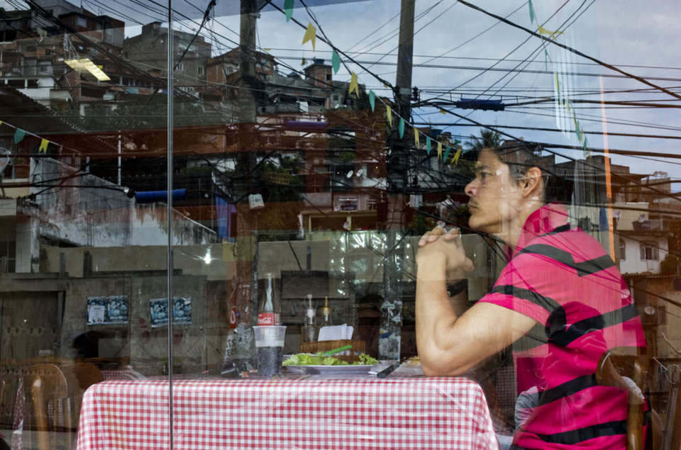 Photo - In this May 22, 2013 photo, a customer eats lunch at Bar Lacubaco in the Vidigal slum, reflected in the window in Rio de Janeiro, Brazil. With its view of the Atlantic's azure waters and its low prices, the Bar Lacubaco could give many conventional Rio restaurants a run for their money. In the land of the $35 martini, where a dinner for two routinely adds up to more than $200, Lacubaco's main courses are just $5-$7 apiece. (AP Photo/Victor R. Caivano)