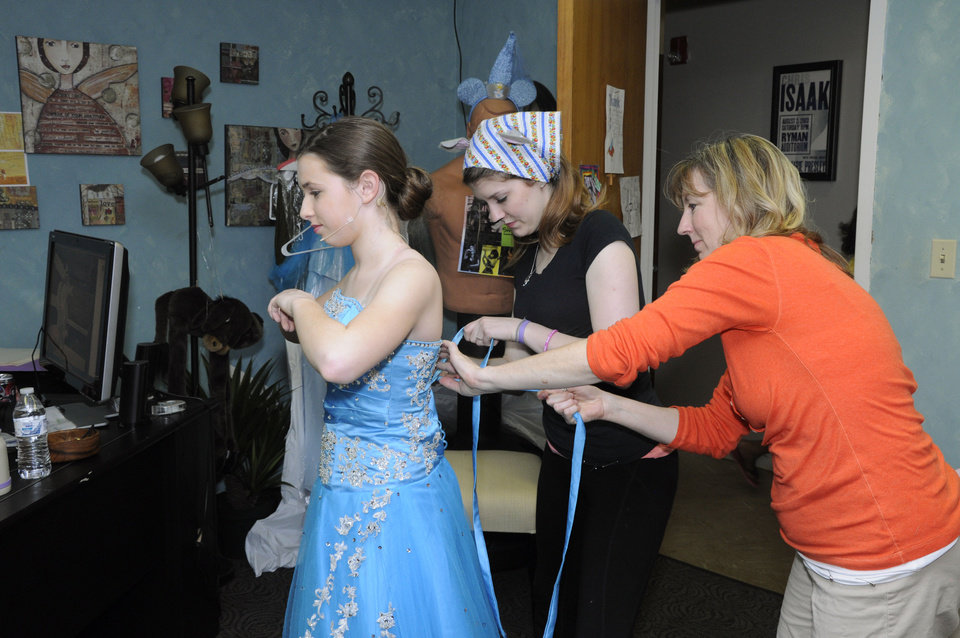 Photo - Lillian Hester is helped into her costume by Madison Linck and director Shawna Linck for the Poteet Theater's