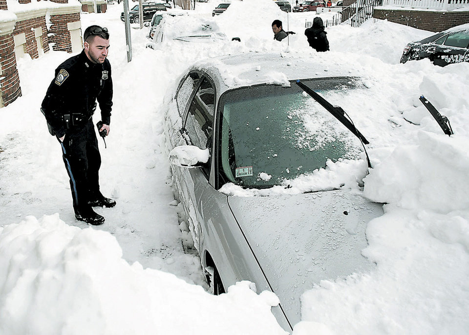 Photo - In this Saturday, Feb. 9, 2013 photo, a Boston Police officer investigates the car where a youth died of carbon monoxide poisoning as he was keeping warm in the Roxbury neighborhood of Boston. Piled snow had blocked the exhaust pipe.  (AP Photo/Boston Globe, John Tlumacki) MANDATORY CREDIT. NO ONLINE USE. MAGS OUT. NO SALES. BOSTON OUT. QUINCY OUT.