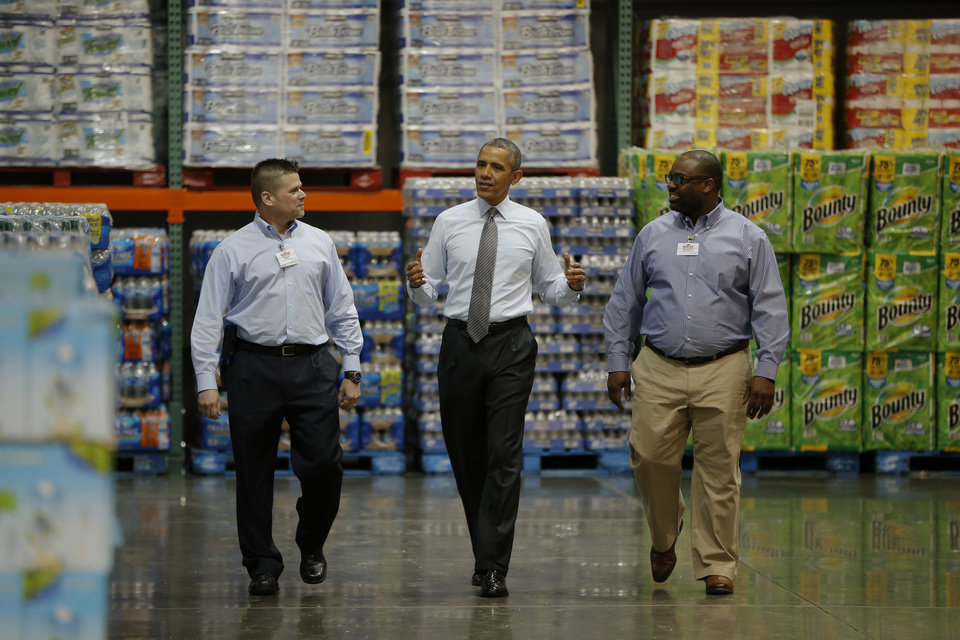 Photo - President Barack Obama walks with Ricky Banner, assistant general manager, right, and Emile (Ray) Quevedo, floor employee, at a Costco store in Lanham, Md., Wednesday, Jan. 29, 2014, before he spoke about raising the minimum wage. The president is promoting his newly unveiled plans to boost wages for some workers and help Americans save for retirement _ no action from Congress necessary. (AP Photo/Charles Dharapak)