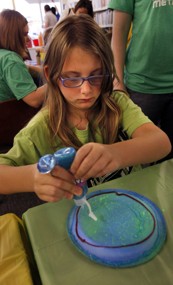 Veronica Hobbs, 8, creates a space-themed art project  during the Summer Reading Program kickoff at Southern Oaks Library on Wednesday.  Photo by Steve Sisney, The Oklahoman <strong>STEVE SISNEY - THE OKLAHOMAN</strong>