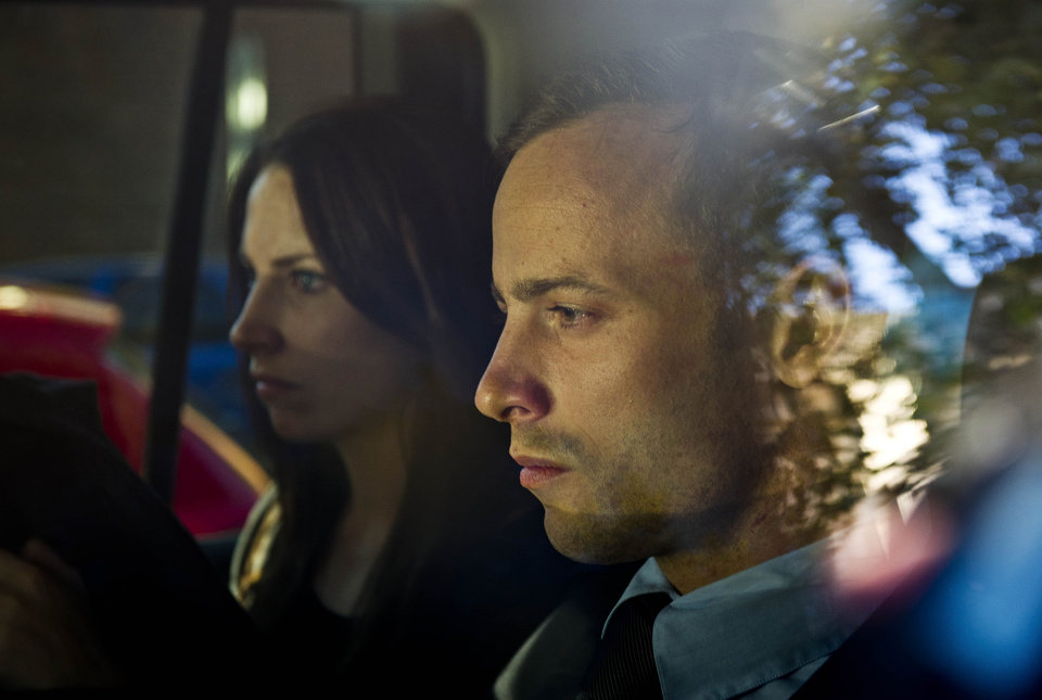 Photo - Olympic athlete Oscar Pistorius, right, and his sister Aimee, left, are driven to a relatives home in Pretoria, South Africa, Friday, Feb. 22, 2013. Pistorius was released on bail and will return to court June, 4, 2013 to face charge a charge of pre-meditated murder in the shooting death of his girlfriend, Reeva Steenkamp. (AP Photo/Nelius Rademan-FOTO24-Beeld) SOUTH AFRICA OUT NO SALES. NO ARCHIVE, ONLINE OUT MAGAZINES OUT INTERNET OUT TV OUT