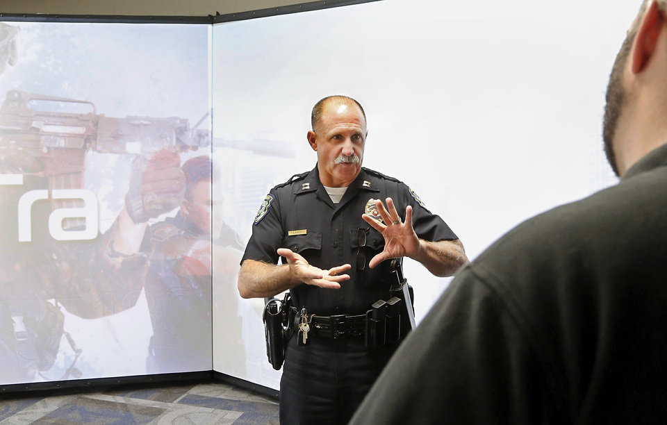 Photo -  Reporter Matt Dinger listens as Capt. Jerry Kennedy explains the way the simulator program functions before taking part in a training scenario on a computerized shooting simulator. [Photo by Jim Beckel, The Oklahoman]