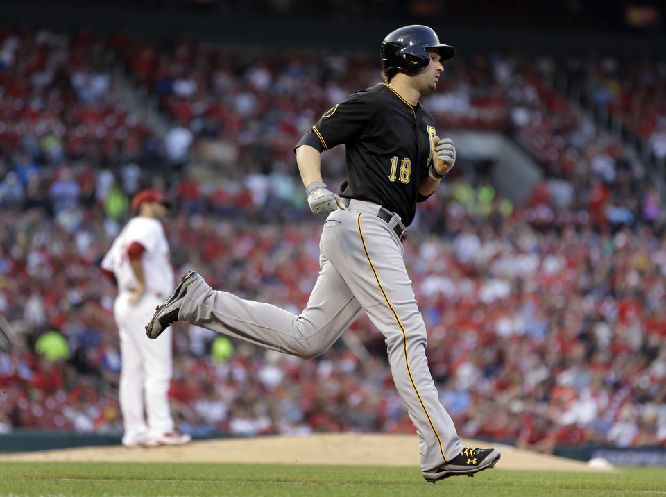 Photo - Pittsburgh Pirates' Neil Walker, right, rounds the bases after hitting a solo home run off St. Louis Cardinals starting pitcher Lance Lynn, left, during the second inning of a baseball game Wednesday, July 9, 2014, in St. Louis. (AP Photo/Jeff Roberson)