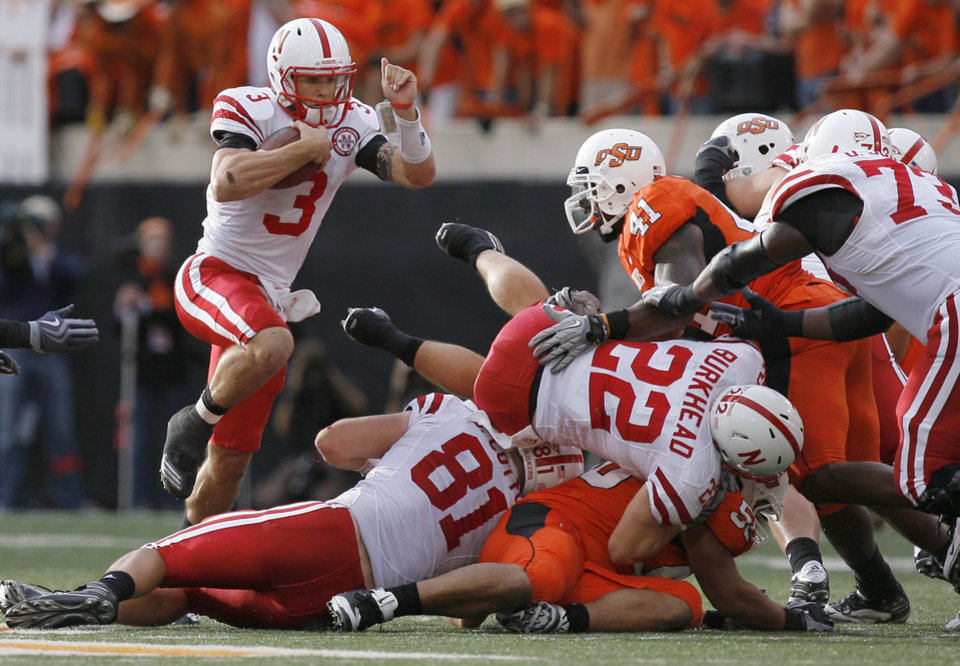 Photo - Nebraska's Taylor Martinez jumps over the pile during the college football game between the Oklahoma State Cowboys (OSU) and the Nebraska Huskers (NU) at Boone Pickens Stadium in Stillwater, Okla., Saturday, Oct. 23, 2010. Photo by Sarah Phipps, The Oklahoman