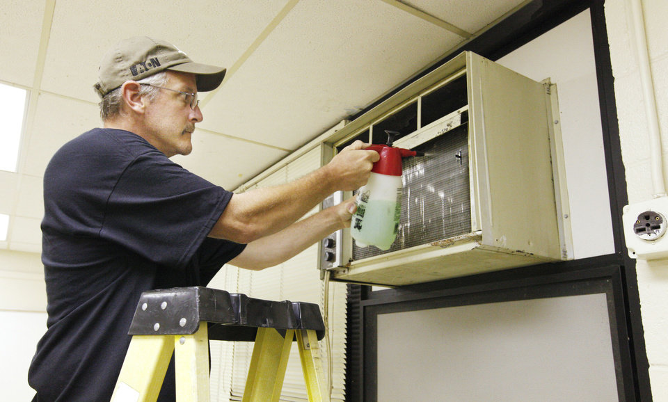 Photo - Maintenance worker Trevor Young cleans an air conditioner during a school beautification project called at  Jarman Middle School in the Mid-Del Public School District. Photo by Paul B. Southerland, The Oklahoman  PAUL B. SOUTHERLAND - PAUL B. SOUTHERLAND