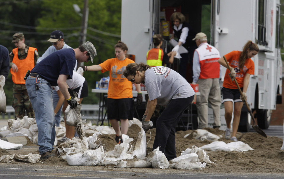 Photo - Volunteers fill sandbags in a church parking for residents to pick-up as floodwaters continue to rise in Evansville, Ind., Wednesday, April 27, 2011. (AP Photo/Darron Cummings)