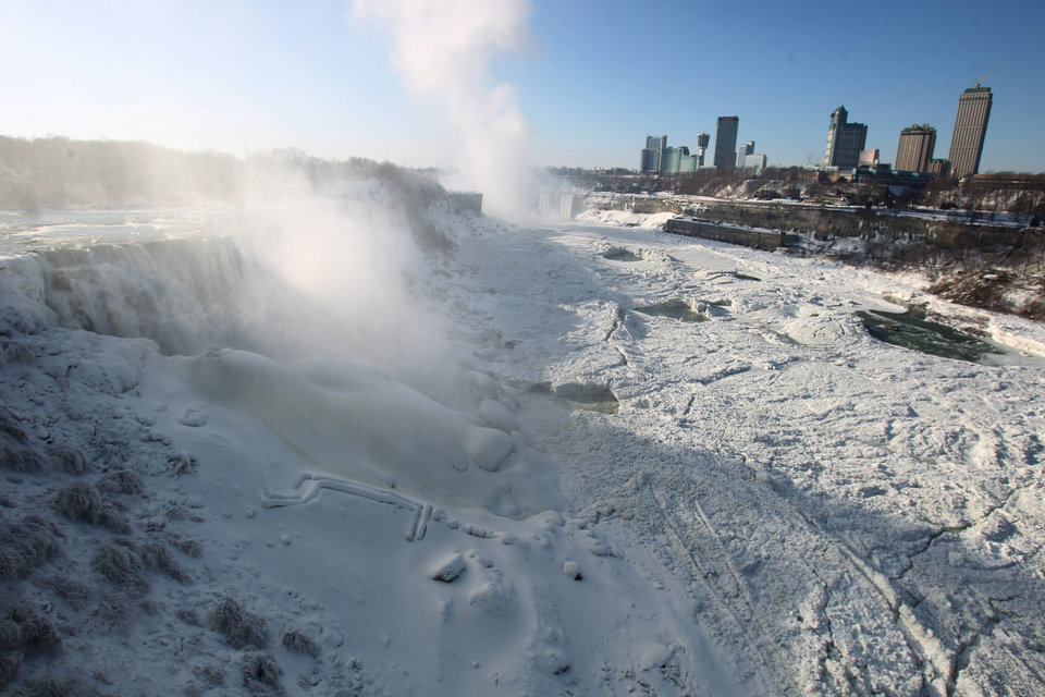 Photo - The area surrounding Niagara Falls, N.Y.,  is coated in a layer of ice in Niagara Falls State Park on Thursday, Jan. 9, 2014. Niagara Falls hasn't frozen over, but it has become an icy spectacle, thanks to a blast of arctic wind and cold that blew around and froze the mist on surfaces and landscaping. Despite the urban legends, Niagara Falls doesn't freeze solid in the winter, tourism officials say.  A section of the American Falls, one of three waterfalls that make up the natural attraction, has frozen. The Niagara River rapids and larger Horseshoe Falls continue to flow unimpeded.  (AP Photo/The Buffalo News, Sharon Cantillon)  MANDATORY CREDIT