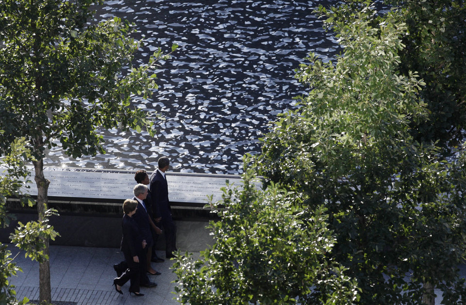 President Barack Obama walks past a reflecting pool with his wife Michelle, and former President George W. Bush and his wife, Laura, as they arrive for the ceremony marking the 10th anniversary of the attacks, Sunday, Sept. 11, 2011 in New York. Two reflecting pools built over the towers' footprints, part of a Sept. 11 memorial that was to open later in the day for relatives of the victims. (AP Photo/Mark Lennihan)